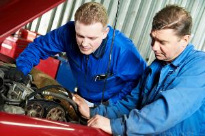 Mechanics adjusting spark plugs
