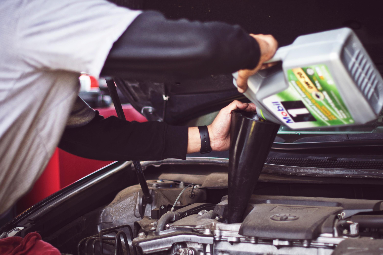 auto mechanic refilling motor oil in car engine